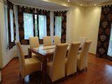 stół w salonie, krzesła pokryte ekoskórą zasłony ekrany firanki, aranżacja