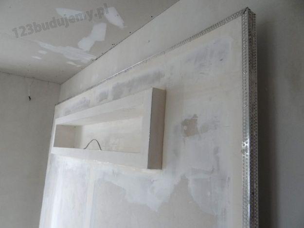 szpachlowanie ozdovbnej półki z regipsu na głośnik basowy i ramki ze zdjęciami w zabudowie telewizora