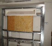 ścianka z wnękami w formie półek tworząca zabudową telewizora
