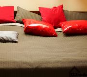 Sypialnia na poddaszu łóżko brązowa narzuta czerwone i brązowe poduszki