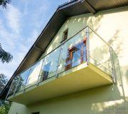 Balkon ze szklaną balustradą z poręczą i słupkami z nierdzewki