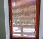 żaluzje brązowe w brązowych oknach białe pomieszczenia