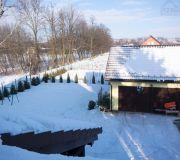 Spadł śnieg, widok na ogród z okna dachowego w sypialni