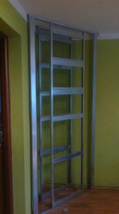 biokominek i półki w narozniku pokoju